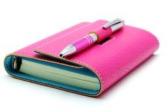 Личный организатор в розовом цвете с ручкой шариковой авторучки на белой предпосылке Стоковые Фотографии RF