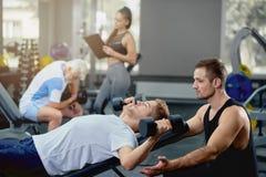 Личный парень порции тренера делая тренировки лежа с гантелями в спортзале стоковая фотография rf