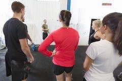 Личный тренер инструктирует его команду разминки фитнеса Стоковое фото RF