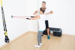 Личный тренер объясняя тренировку фитнеса Стоковое фото RF