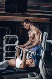 Личный тренер помогая молодой женщине поднять штангу пока разрабатывающ в спортзале Стоковая Фотография RF