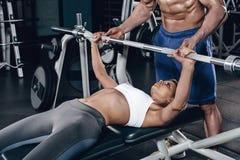 Личный тренер помогая молодой женщине поднять штангу пока разрабатывающ в спортзале Стоковая Фотография