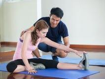 Личный тренер при привлекательная азиатская женщина делая exercis Стоковое фото RF