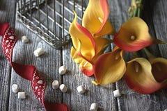 Лилии calla оранжевого желтого цвета с красной лентой и белые зефиры на деревянной серой предпосылке Стоковое фото RF