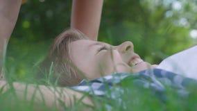 Лоб прелестной маленькой девочки портрета конца-вверх целуя мальчика лежа в траве Несколько счастливые дети Смешной видеоматериал