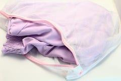 Ловит сетью сумку прачечной, для моя одежд в стиральной машине на белой предпосылке Стоковое Фото