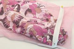 Ловит сетью сумку прачечной, для моя одежд в стиральной машине на белой предпосылке Стоковое Изображение