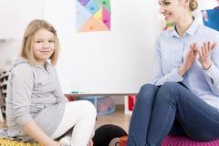 Логопед усмехаясь на маленькой девочке стоковое фото