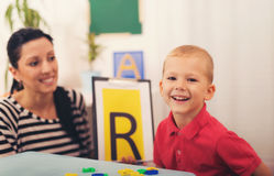 Логопед учит, что мальчики говорят письмо стоковые фото