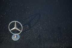 Логотип звезды Benz Мерседес стоит вверх на влажном клобуке автомобиля в росе утра стоковые изображения