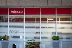 Логотип Adecco перед их главным офисом для Сербии Adecco швейцарская группа специализированная в комплектовать штаты, промежутке  стоковая фотография rf