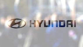 Логотип Hyundai Мотора Компании на стекле против запачканной толпы на steet Редакционный перевод 3D сток-видео