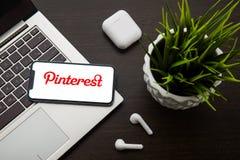 Логотип Pinterest на экране iphone x помещен на клавиатуре ноутбука рядом с AirPods стоковые фотографии rf