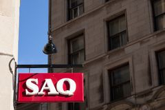 Логотип SAQ на их главном магазине для центра Монреаля Также как des Alcools du Квебек, sekking духи, alcool, вино & пиво Societe стоковая фотография
