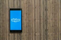 Логотип Skype на экране smartphone на деревянной предпосылке Стоковые Изображения RF