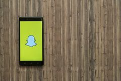 Логотип Snapchat на экране smartphone на деревянной предпосылке Стоковое Фото