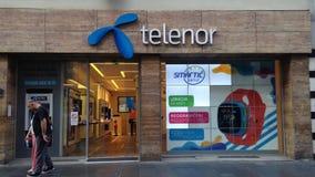 Логотип Telenor перед их главным магазином в Белграде, с ATM от банка Telenor Banka сток-видео