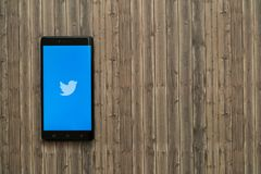 Логотип Twitter на экране smartphone на деревянной предпосылке Стоковые Изображения