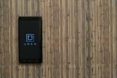 Логотип Uber на экране smartphone на деревянной предпосылке Стоковое фото RF