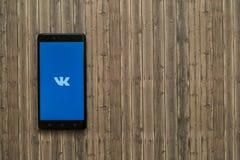 Логотип Vkontakte на экране smartphone на деревянной предпосылке Стоковое Изображение RF