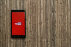 Логотип Youtube на экране smartphone на деревянной предпосылке Стоковое Изображение RF