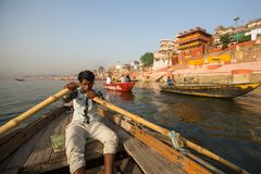 Лодочники на шлюпке скользят через воду на Ганге вдоль берега Варанаси Стоковые Фото
