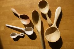 6 ложек высекаенных рукой деревянных аранжировали на таблице в солнце Стоковые Изображения RF