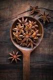 Ложка анисовки звезды на темной деревенской деревянной предпосылке Стоковые Изображения