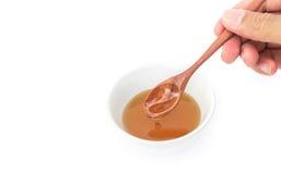 Ложка владением руки крупного плана деревянная льет мед на белой предпосылке, h Стоковое Фото