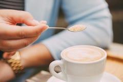 Ложка в сахаре женской руки лить в ее кофейную чашку Стоковая Фотография