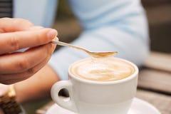 Ложка в сахаре женской руки лить в ее кофейную чашку Стоковые Изображения RF