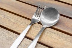 Ложка и вилка для едят на деревянном столе Стоковые Изображения
