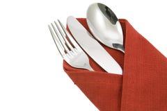 Ложка и нож вилки на красной изолированной салфетке Стоковые Изображения