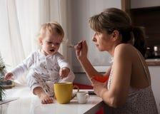Ложка мати подавая ее ребёнок стоковые изображения