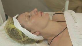 Ложь взрослой женщины в салоне красоты под белым одеялом Анти- slincare вызревания сток-видео