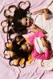 Ложь девушек на розовой предпосылке простынь Школьницы в пижамах стоковые фото