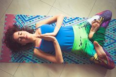 Ложь женщины на циновке йоги с руками в жесте и ногах namaste внутри Стоковое Фото