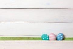 Ложь 3 красочная handmade пасхальных яя handmade на зеленой лужайке на белой деревянной предпосылке с космосом вышла Стоковое Фото