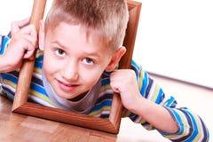 Ложь мальчика на поле и игра с рамкой Стоковое Фото