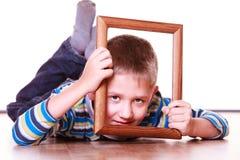 Ложь мальчика на поле и игра с рамкой Стоковое Изображение