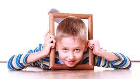 Ложь мальчика на поле и игра с рамкой Стоковая Фотография