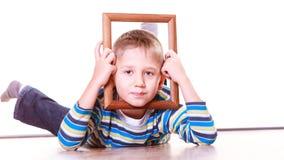 Ложь мальчика на поле и игра с рамкой Стоковые Фотографии RF