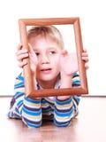Ложь мальчика на поле и игра с рамкой Стоковая Фотография RF