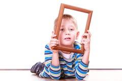 Ложь мальчика на поле и игра с рамкой Стоковое фото RF