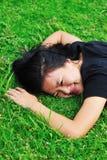 Ложь молодой женщины на траве Стоковое Изображение