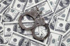Ложь наручников полиции на много долларовых банкнотах Концепция противозаконного владения денег, противозаконных сделок с доллара стоковые изображения