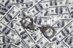 Ложь наручников полиции на много долларовых банкнотах Концепция противозаконного владения денег, противозаконных сделок с доллара стоковое фото