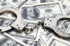 Ложь наручников полиции на много долларовых банкнотах Концепция противозаконного владения денег, противозаконных сделок с доллара стоковое изображение rf