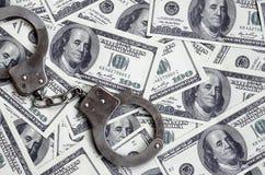 Ложь наручников полиции на много долларовых банкнотах Концепция противозаконного владения денег, противозаконных сделок с доллара стоковая фотография
