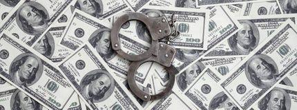 Ложь наручников полиции на много долларовых банкнотах Концепция противозаконного владения денег, противозаконных сделок с доллара стоковая фотография rf